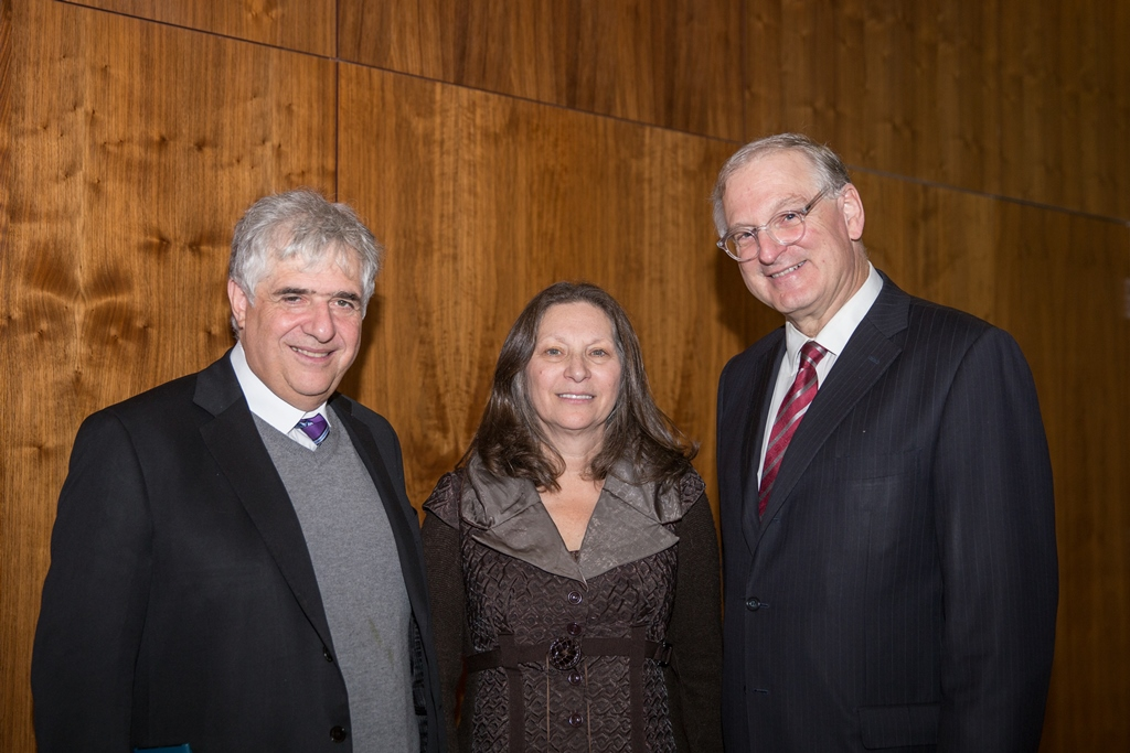 Two men and a woman stand in front of a wood-panelled wall. The man on the left wears a sweater beneath his suit jacket and the man on the right wears glasses.