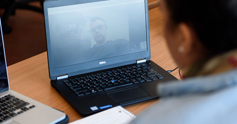 Young woman talking to a colleague through her laptop.