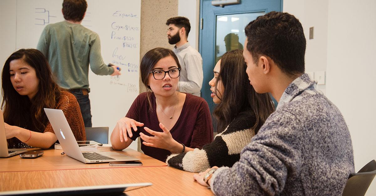 Plusieurs étudiants discutent dans une salle de cours