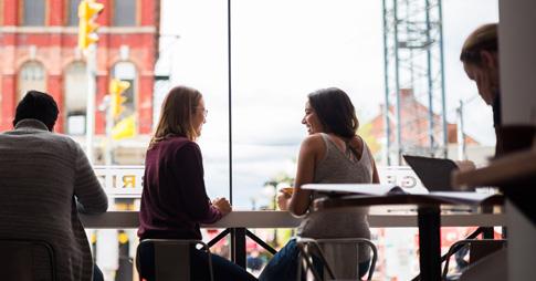 Des étudiants vus de dos, assis dans un café.