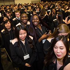 Une foule de diplômés souriants portant des robes.