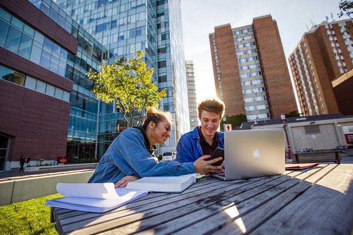 Deux étudiants assis dehors à une table