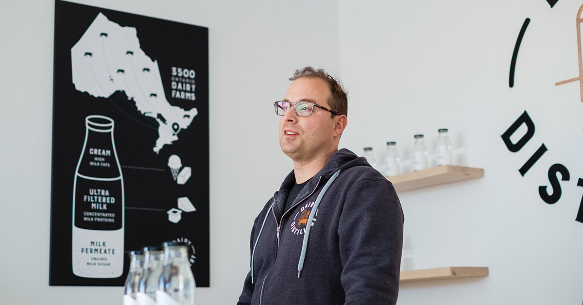 portrait of Omid Mcdonald as he stands in at the bar of the Dairy Distillery