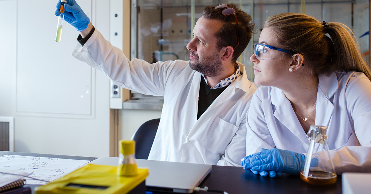 professor Alexandre Poulain looks at yellow yeast sample in test tube to verify clarity with Jessica Gaudet