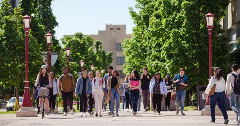 A group of students walking outside, on campus.