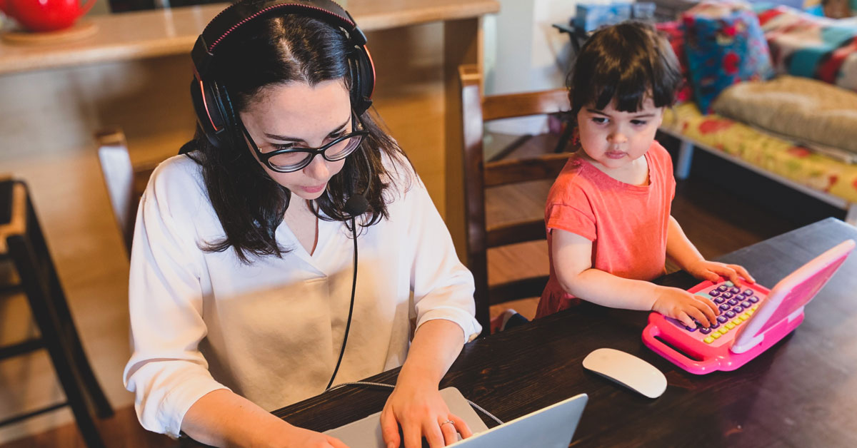 A woman working on her laptop as her young daughter sits beside her, playing on a toy computer.