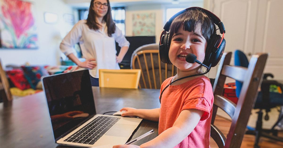 Une une fillette porte des écouteurs sur sa tête. Elle est assise devant un ordinateur portable alors que sa mère l'observe au loin.