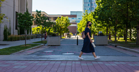 Étudiante portant un masque et marchant dans un campus vide