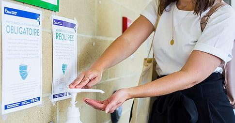 une femme utilise un désinfectant pour les mains tout en portant un masque facial