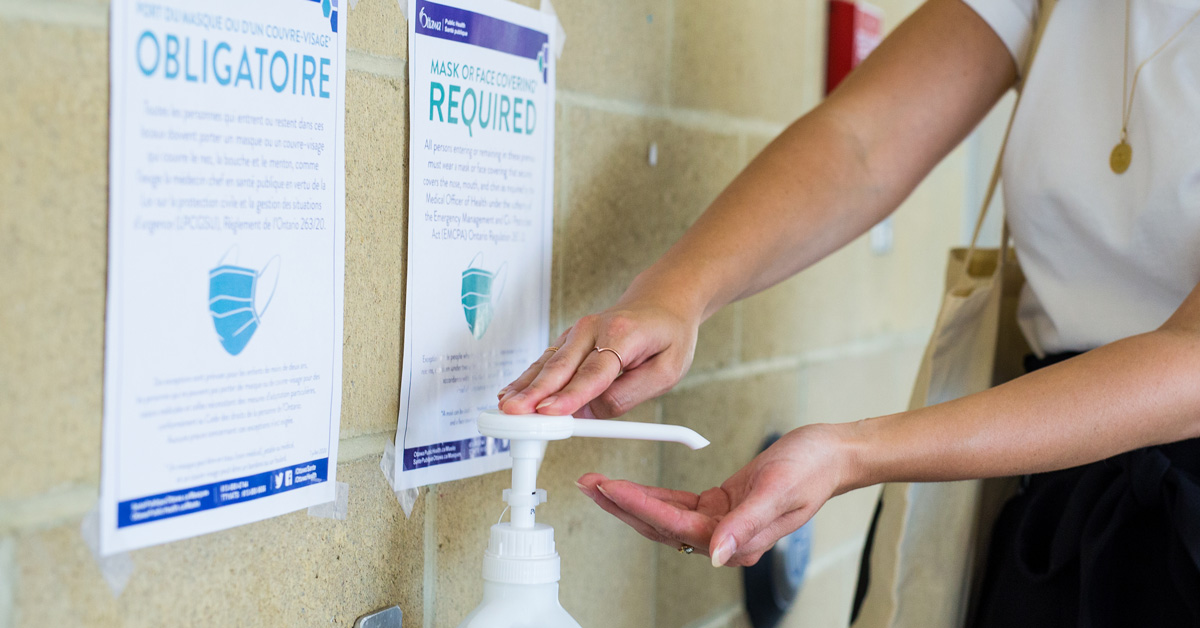 A person presses a hand sanitizing gel pump.