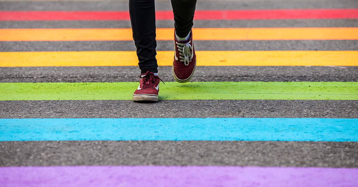 Student walking across the pride crosswalk on campus