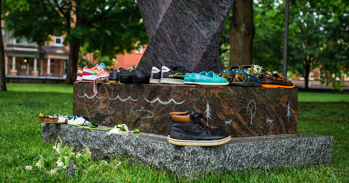 Several pairs of shoes placed around the Indigenous sculpture on Tabaret lawn.