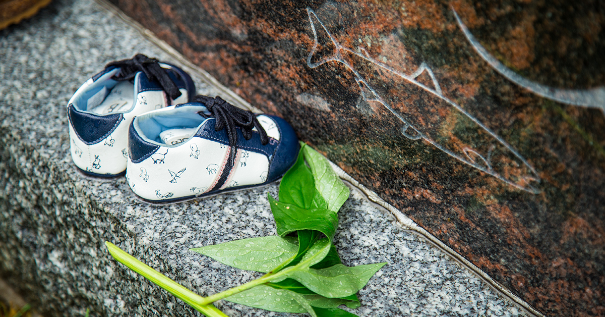 Close-up of a pair of baby shoes placed on the Indigenous sculpture on Tabaret lawn.