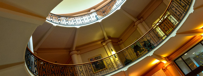 The upper reach of Tabaret Hall's rotunda reveals elegant architecture and wrought iron railings with filigree.