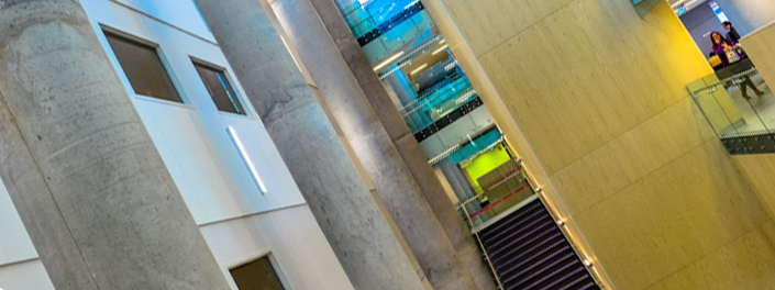 An artistically photographed view of the bright inside of uOttawa's Learning Crossroads building with its tall concrete columns, glass features and a stairwell.