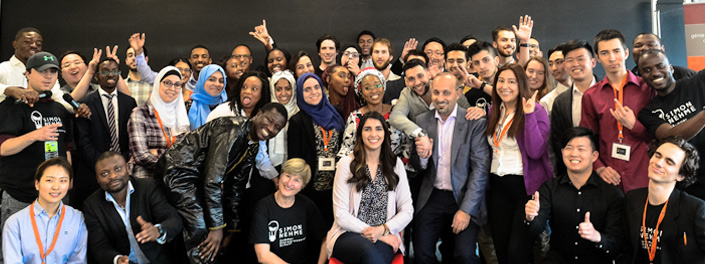 A large global group of men and women happy about their graduation from an entrepreneurship program.