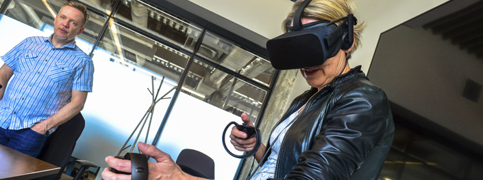 A women experiences 3D virtual reality by using hand controls and wearing an eye mask resembling scuba diving goggles.