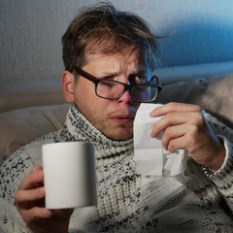 Man looking dishevelled holding a tissue and mug.