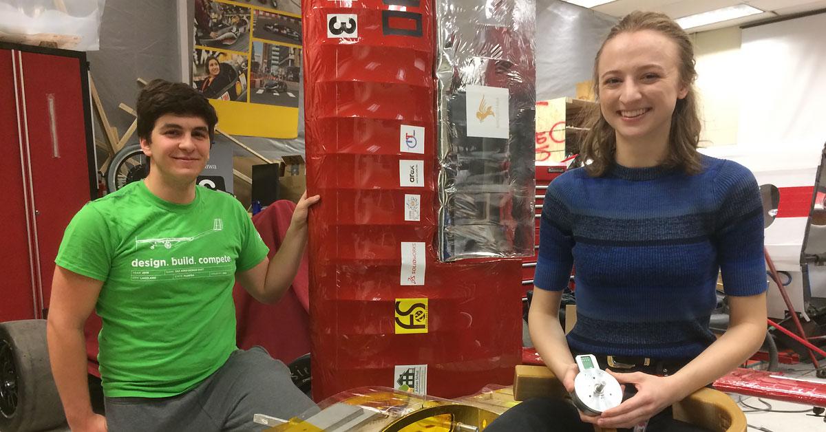 Matt Sehri est agenouillé près d'un modèle d'aéronef, une main posée sur son aile. Sarah Horton, souriante, est assise sur un tabouret et tient à la main un moteur et un membre robotisé recourbé.