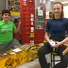University of Ottawa student Matt Sehri beside a model of an aircraft, holding its wing. University of Ottawa student Sarah Horton sits on a stool, smiling and holding a motor and a curved robotic limb.