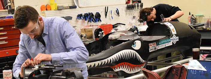 Un homme portant des lunettes de sécurité se penche sur un étau, tandis qu'un second travaille sur la carrosserie d'un véhicule où des dents et des yeux de requin ont été peints. L'atelier où ils travaillent est garni de pinces et de tournevis, et un ordi