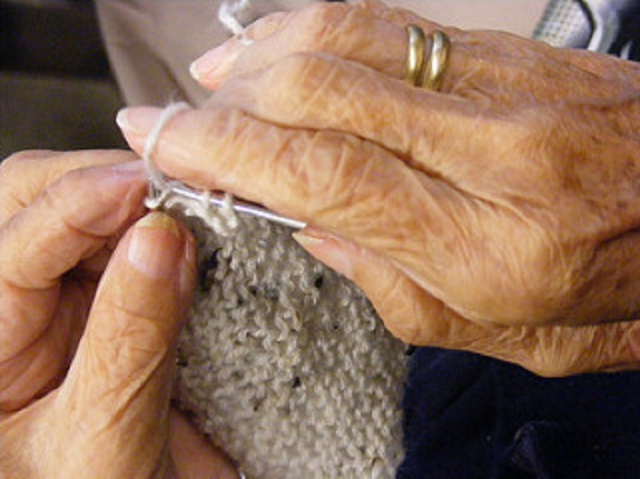 Close-up shot of the hands of an older woman, knitting