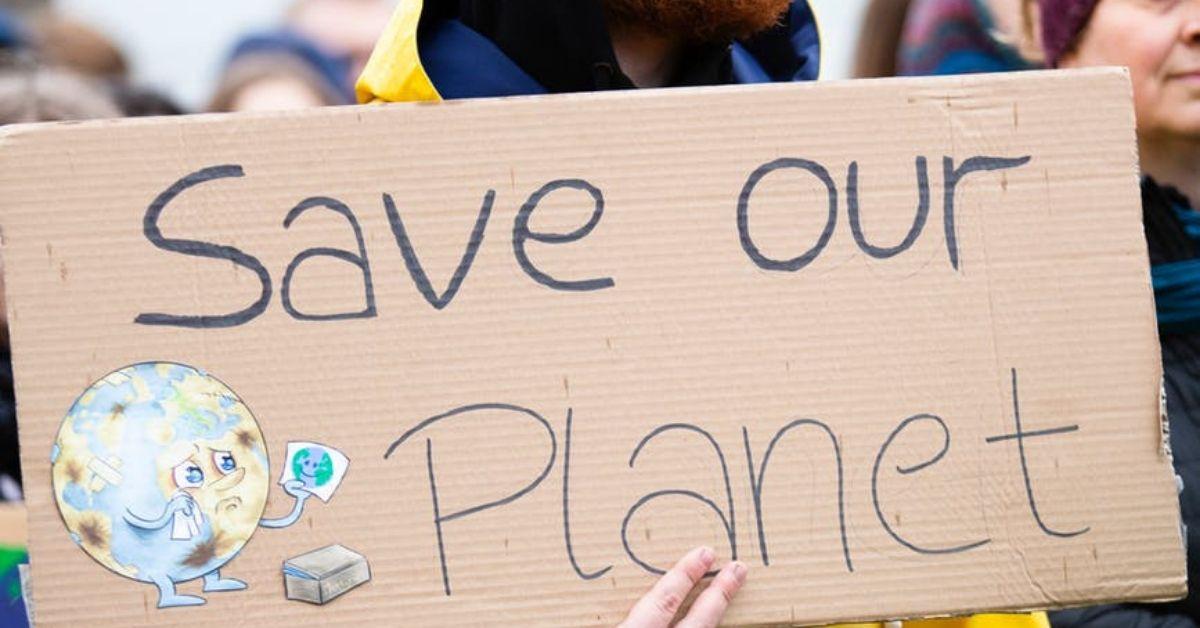 Une affiche en carton sur laquelle est écrit «Sauver la planète»