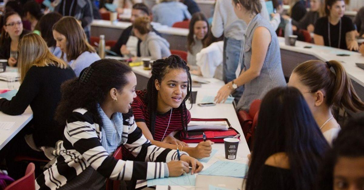 Des étudiantes jasent dans une salle de classes.