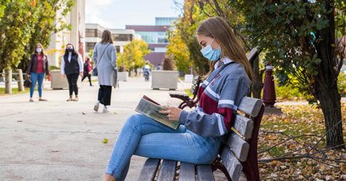 Une étudiante lit un livre à l'extérieur sur le campus.