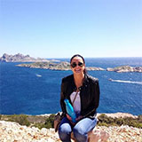 caitrd assise sur des rochres devant l'océan un jour ensoleillé