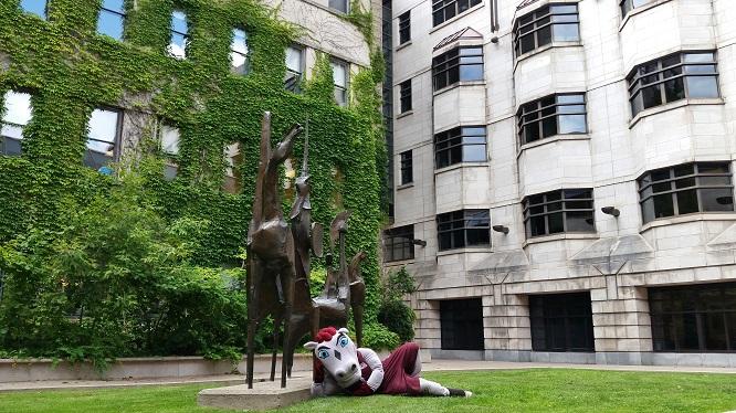 La mascotte Gee-Gee étendu au sol devant une sculpture.