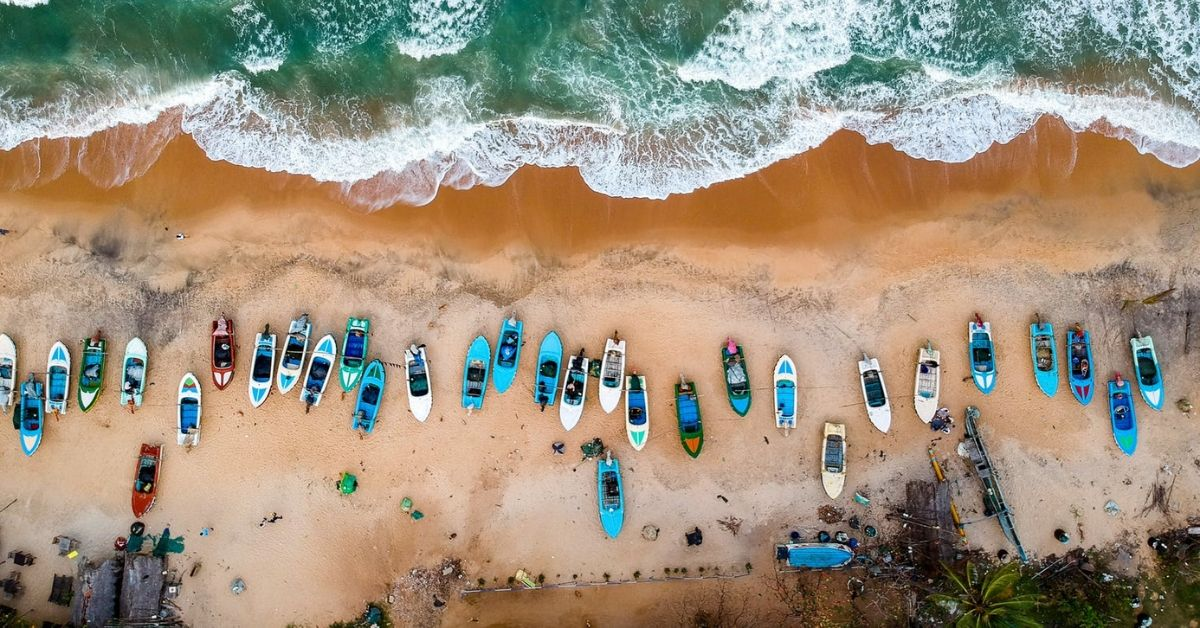 A bird-eye view of a beach with a canoes of different colours lineup on the beach