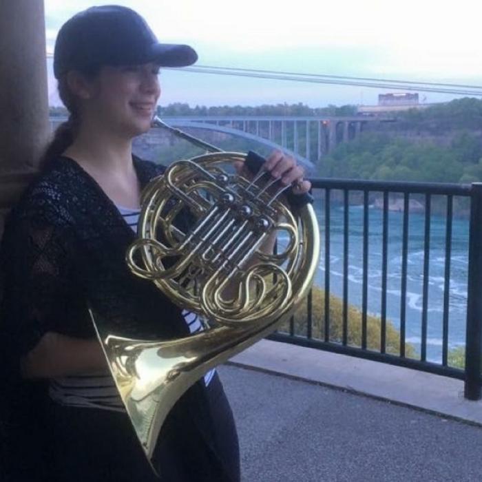 chantalprousse au bord d'une rivière qui tient un cor français