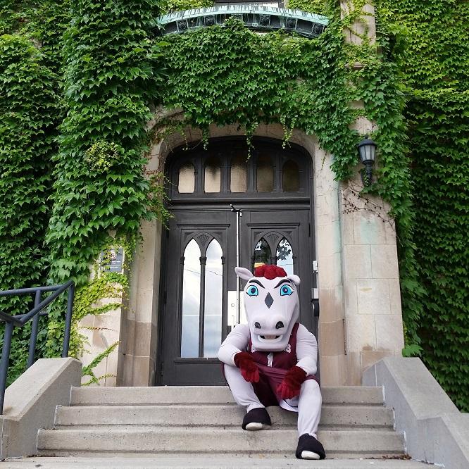 La mascotte Gee-Gee assis devant l'entrée du pavillon Hagen.