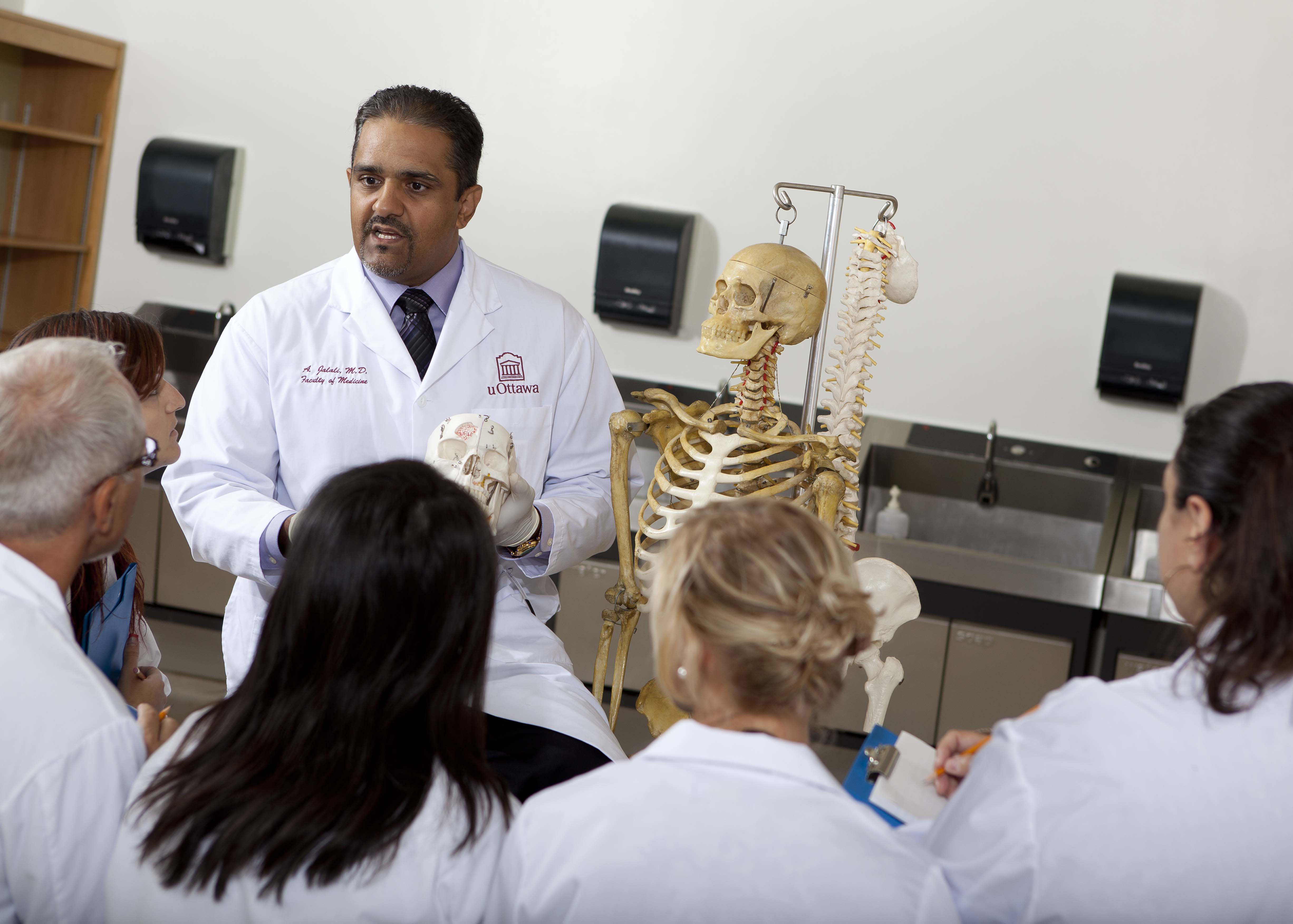 A man in a lab coat stands beside an anatomical skeleton model in a medical teaching lab. He is talking to a group of five people, also in lab coats.
