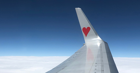 plane wing with red heart painted on it ,blue sky and clouds from passengers perspective