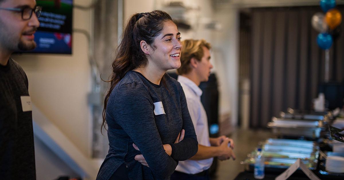 Une jeune femme, souriante, discute lors d'un événement.