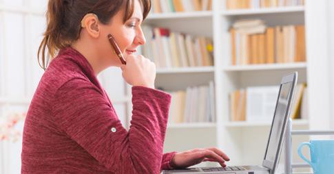 Une femme portant une oreillette, assise devant un ordinateur portable.