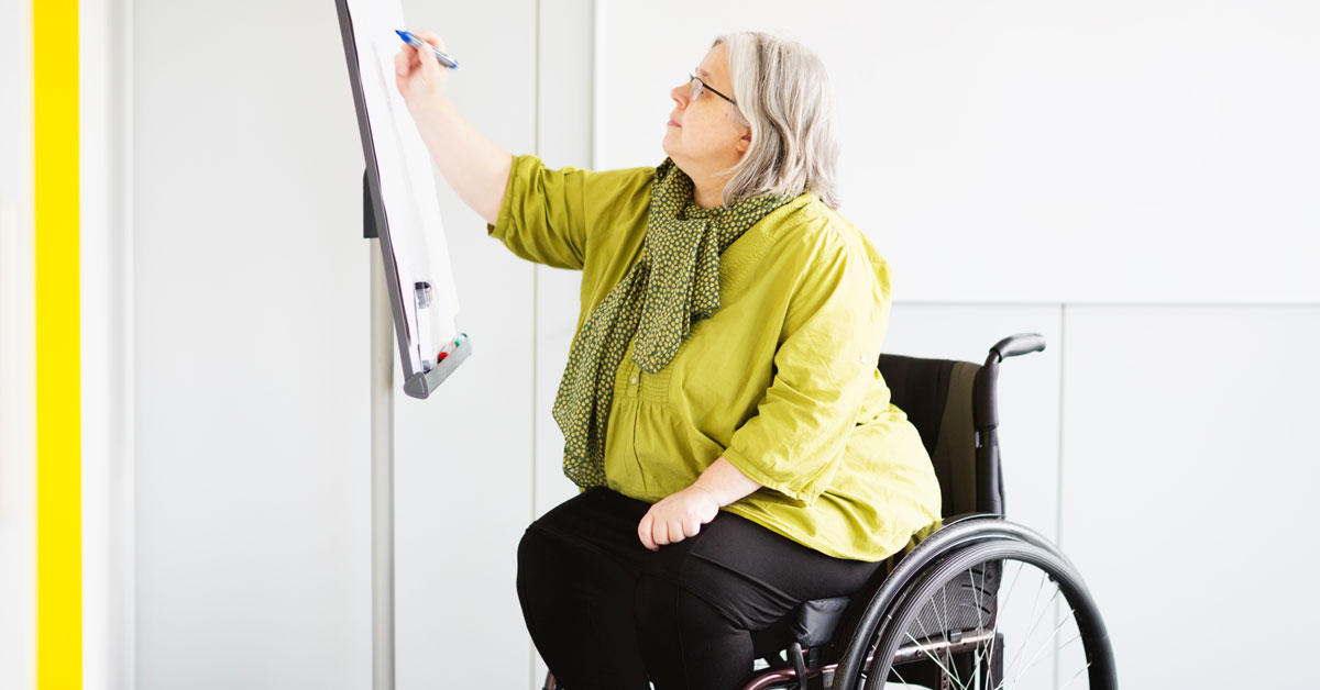 A woman in a wheelchair writing on a whiteboard.