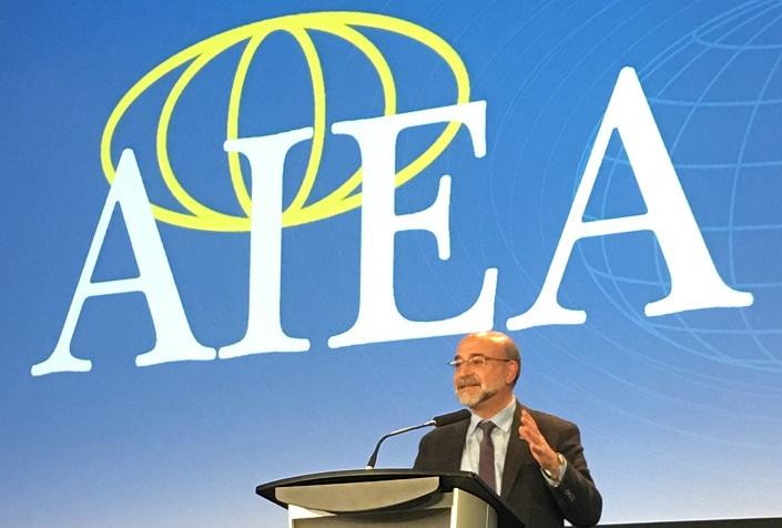 Adel El Zaïm debout derrière un lutrin, sous une bannière de l'AIEA.