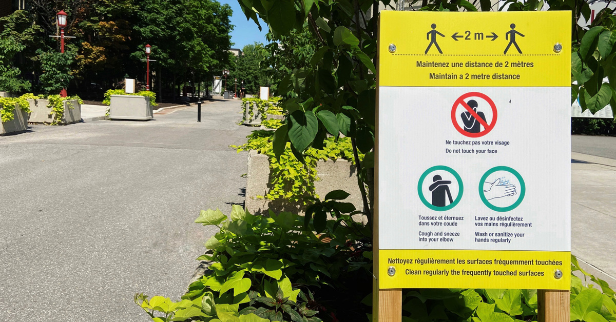 A pedestrian street on campus with an outdoor sign with instructions to prevent the spread of the virus