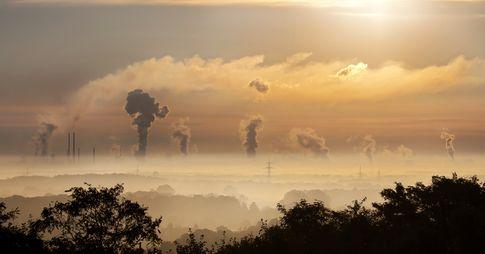 Paysage où l'on aperçoit au loin des cheminées industrielles qui jettent de la fumée