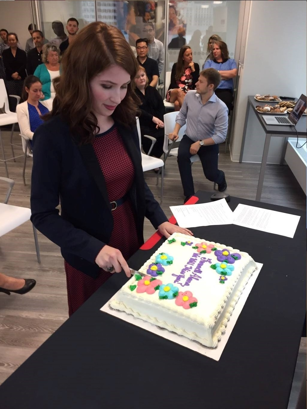 Couvrette cutting a cake with a group of people behind her