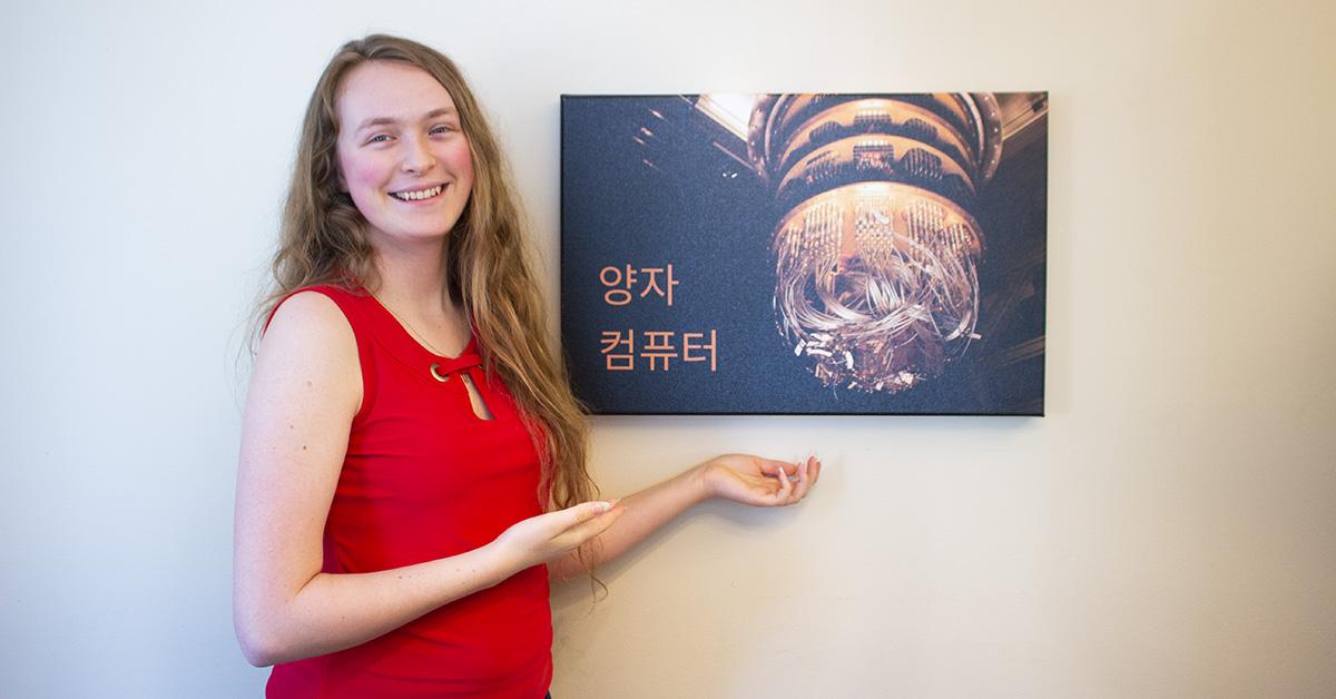 Angéline Lafleur stands next to a mounted photograph of a quantum computer.