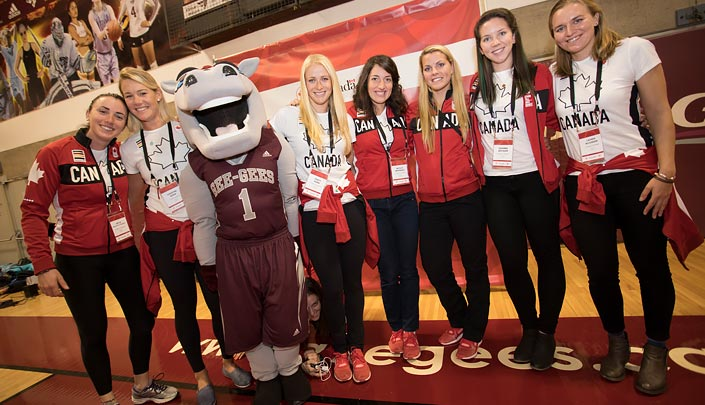 Line of female athletes posing with a person dressed in a horse costume