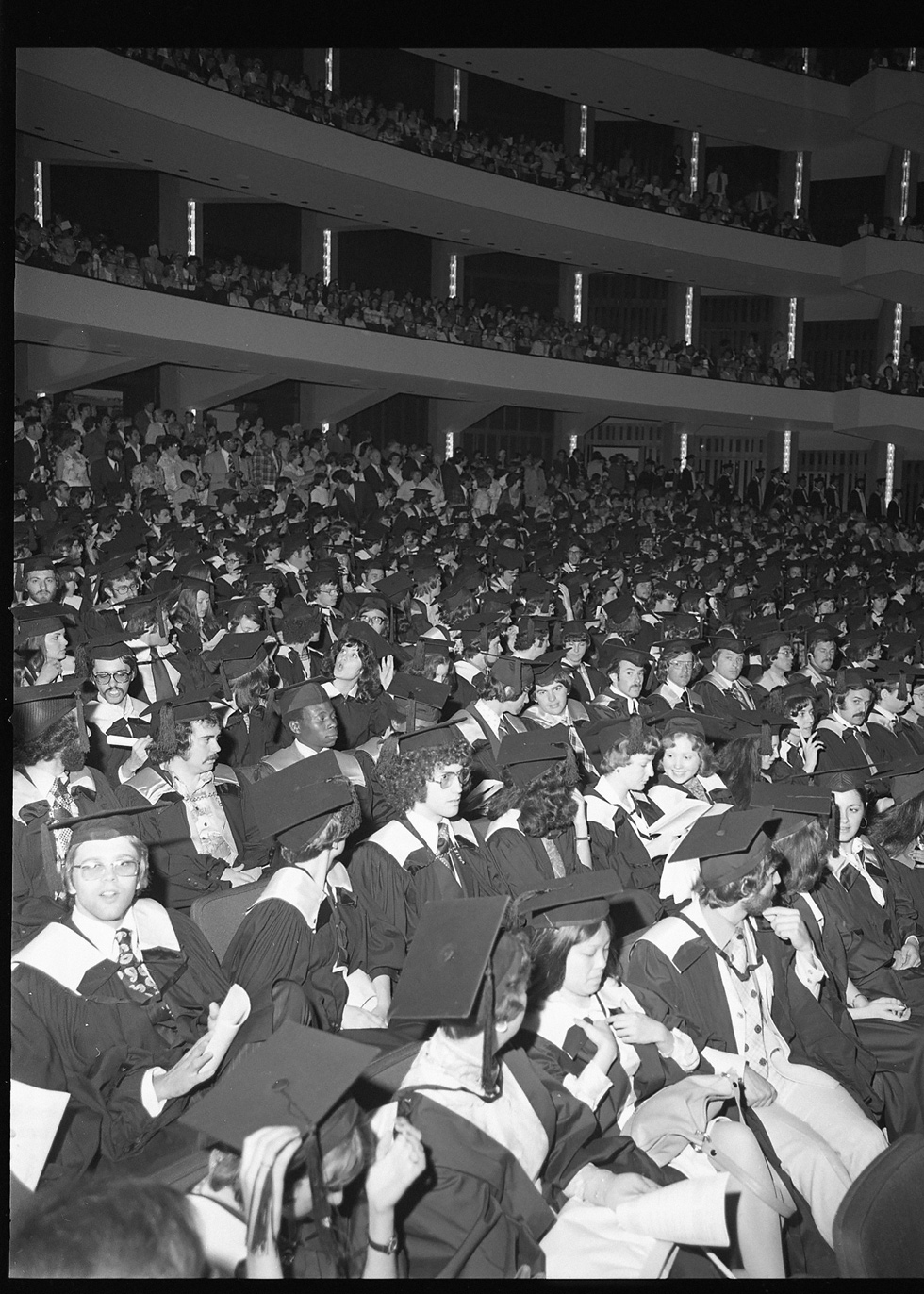 Black and white photo of a theater full of students dressed in graduation gowns and mortar boards in 1976.