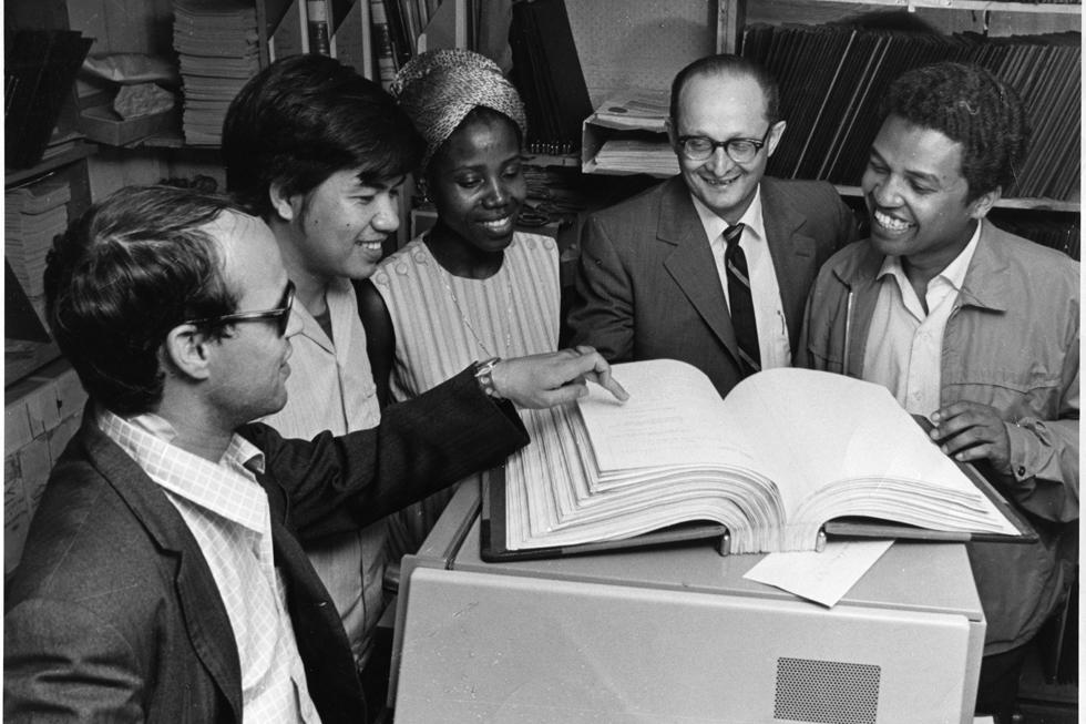Black and white photo four men and a woman looking at large open book.