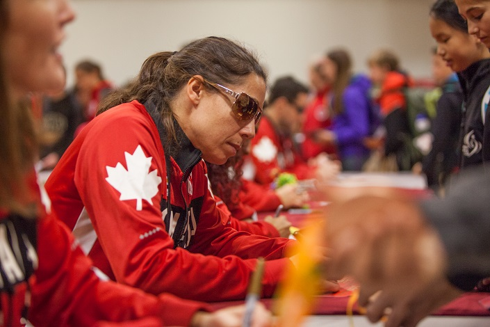A woman wearing sunglasses and red jackets with a maple leaf on the arm.