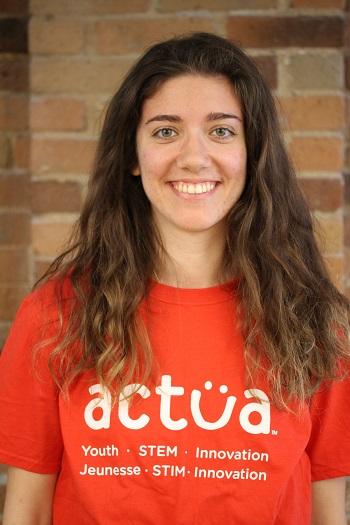 Une jeune femme souriante porte un tee-shirt d'Actua.