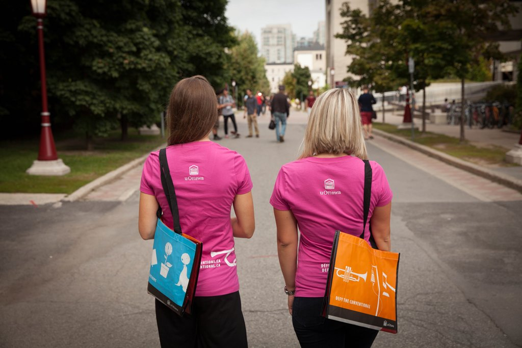 Two women wearing uOttawa Defy the Conventional T-shirts with tote bags over their shoulders, walking away down a pathway.